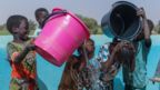 Children wash and play in clean water at a WaterAid pump
