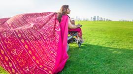 Nawaal Akram in wheelchair, wearing a flowing pink shawl.