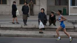 Runner watched by passers-by