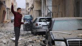 A man gestures while standing amidst debris in the Syrian Kurdish town of Jandairis in the northern Afrin district