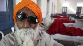 A man sits on a bed while waiting for treatment at a hospital after undergoing cataract removals from a free eye surgery camp, in the northern Indian city of Amritsar