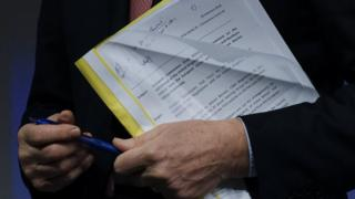 Michel Barnier holding the EU draft withdrawal agreement document in a plastic folder